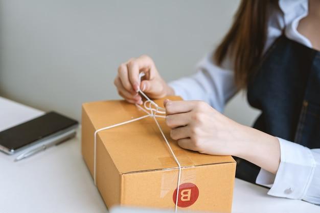 顧客のために小包を梱包している小さなオンラインビジネスの所有者の手のクローズアップ。