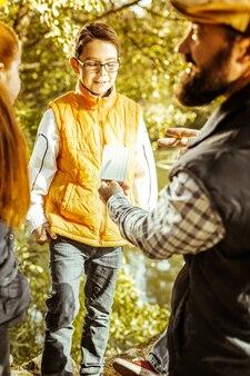 Крупным планом маленький ученик в очках и оранжевом жилете во время экологического урока в лесу в хороший день