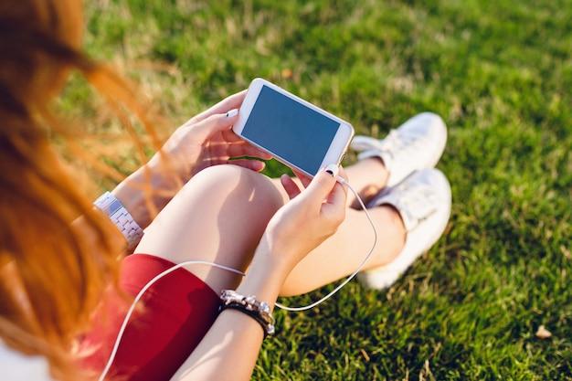 女の子の手の中のスマートフォンのクローズアップ。赤いスカートと白いスニーカーを身に着けている緑色のガラスに座っている女の子