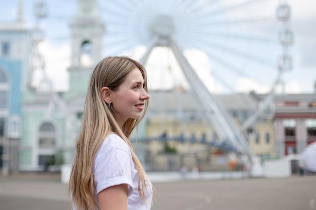 Крупный план улыбающейся блондинки в белой футболке, смотрящей в сторону на фоне колеса обозрения на улице