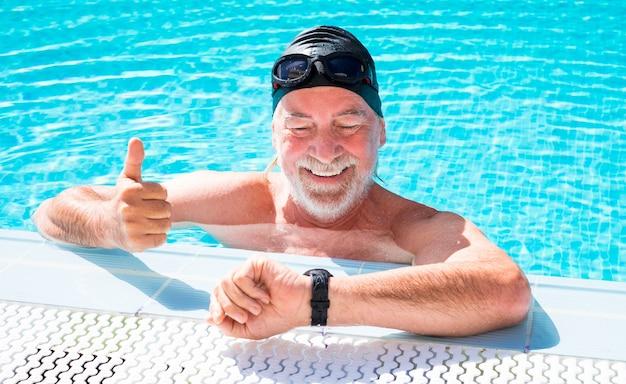 스포츠를 하 고 파란색 수영장에서 수영 웃는 수석 남자의 클로즈업. 만족스럽게 스톱워치를 확인합니다. 흰 수염과 그의 수영에 행복 콧수염을 가진 남자. 건강한 생활.