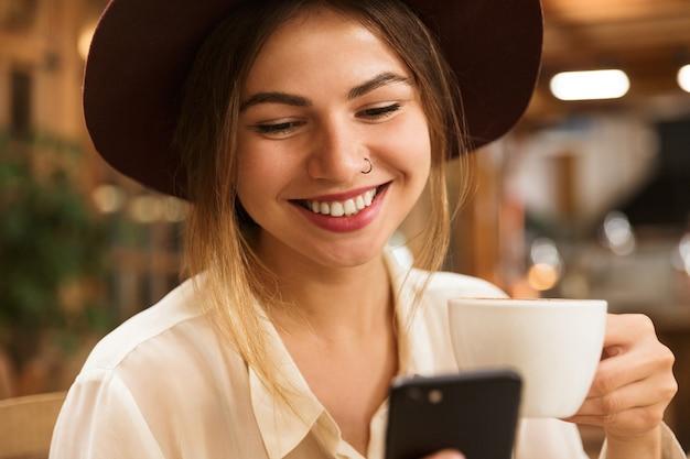 Крупным планом улыбается женщина в шляпе, сидя за столиком в кафе