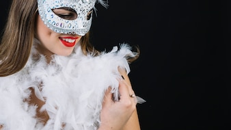 Close-up of a smiling woman with carnival mask and boa feather on black background
