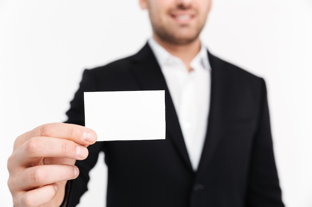 Крупным планом улыбающийся молодой бизнесмен, одетый в костюм