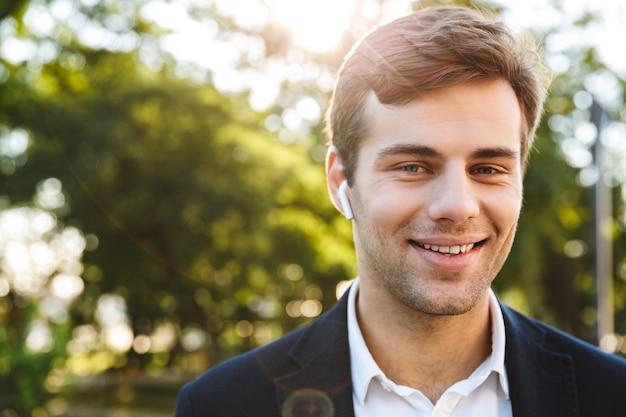 イヤホンを着用して、屋外を歩いている笑顔の青年実業家のクローズアップ