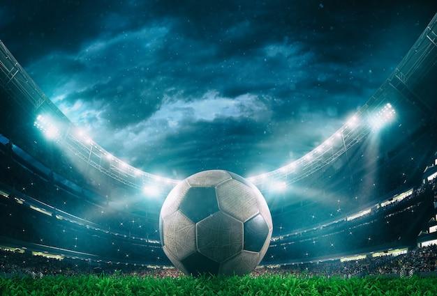 헤드 라이트에 의해 조명 경기장의 중앙에 축구 공의 닫습니다