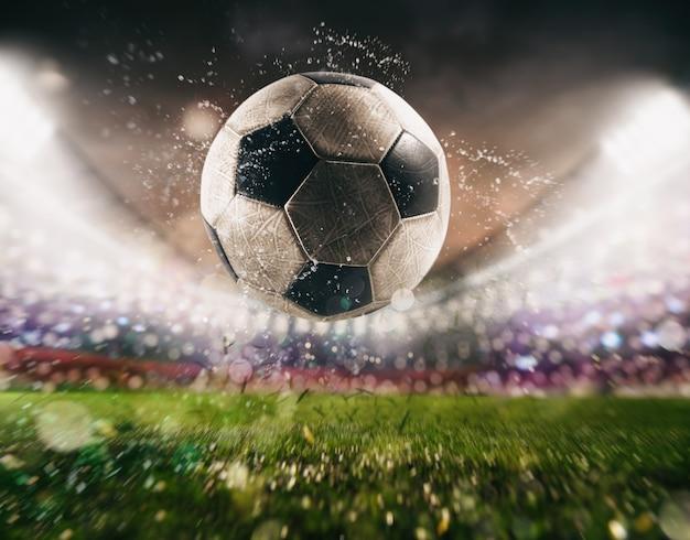 スタジアムで力を込めて蹴られたサッカーボールのクローズアップ