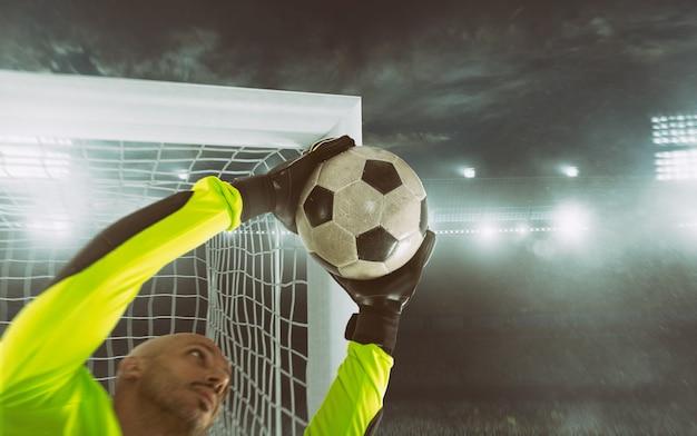 ゴールポストの隅にボールを保存しているサッカーのゴールキーパーのクローズアップ