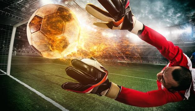 燃えるようなボールをキャッチしようとしているゴールキーパーとの夜の試合でサッカーシーンのクローズアップ