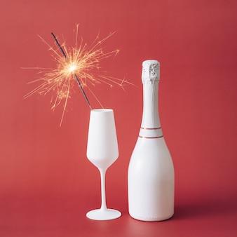 新年のお祝いの喜びの象徴としてコピースペースの赤い背景にラベルのないシャンパンのボトルの横にある白いフルートの線香花火のクローズアップ