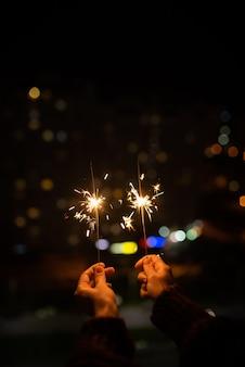 행복한 소녀의 손에 있는 향의 클로즈업. 크리스마스와 새해를 축하합니다. 휴일