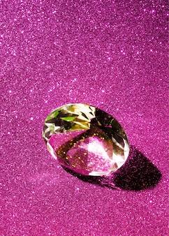 ピンクの光沢のある背景に輝くダイヤモンドのクローズアップ