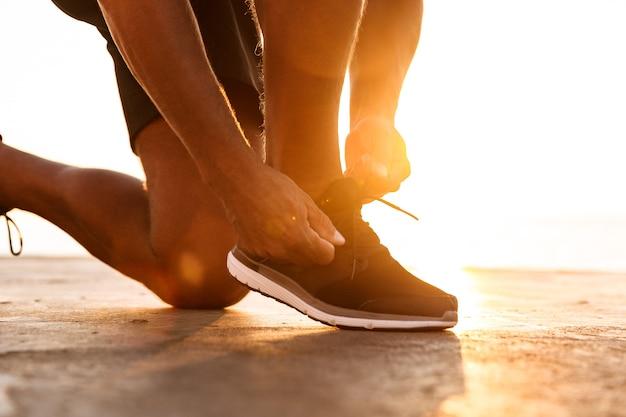 彼の靴ひもをマンティするスポーツマンのクローズアップ