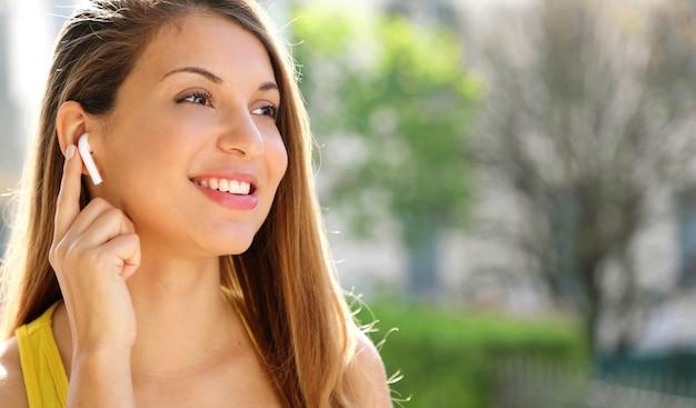 外のワイヤレスイヤホンを接続するスポーティな笑顔の女の子のクローズアップ。サイドコピースペースエリアを探しています。