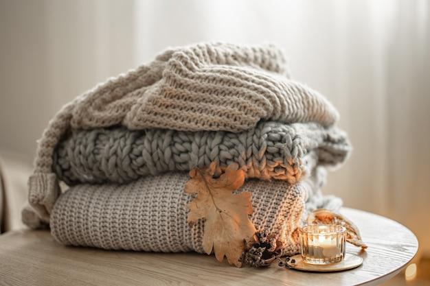 Крупный план стека вязанных свитеров на размытом фоне.