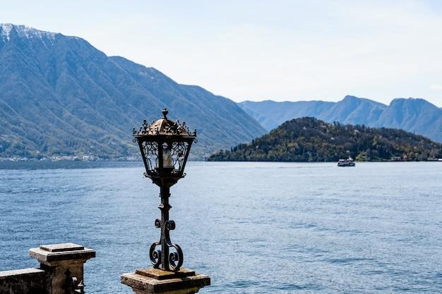 Крупный план уличного фонаря на фоне гор и воды озера комо в италии.