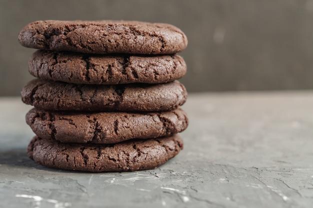 暗い背景にサクサクのチョコレートクッキーのスタックのクローズアップ。テキストのスペースをコピー