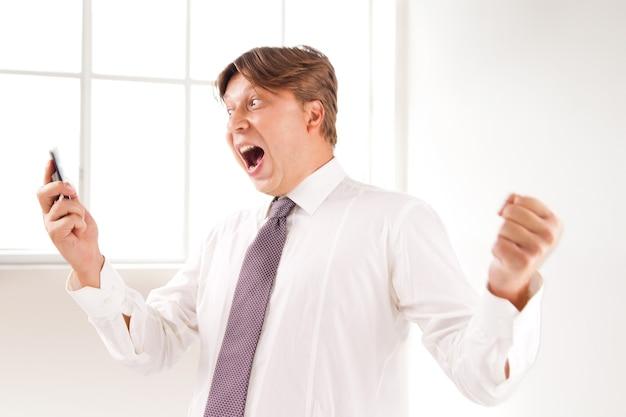 그의 사무실에서 전화로 성공하고 웃는 사업가의 클로즈업