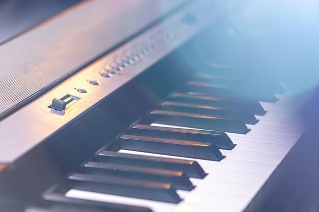 美しい舞台照明でのシンセサイザーまたはピアノの鍵盤のクローズアップ。