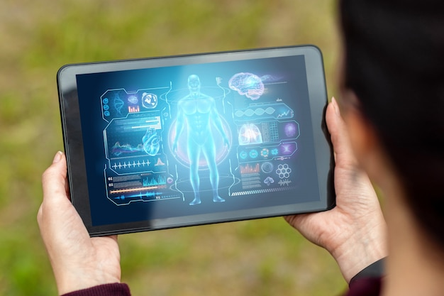 医療技術のホログラムグラフィックスを描いた手のタブレットのクローズアップ。現代の医学。
