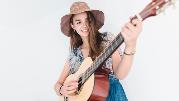 ギター、帽子をかぶっている、才能のある10代の少女のクローズアップ