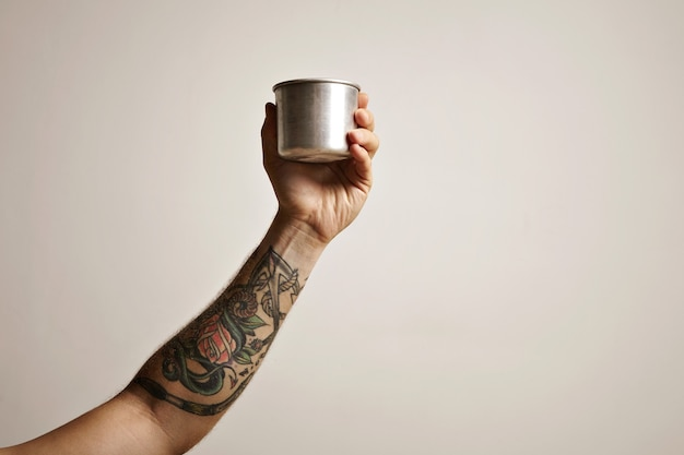 白い代替コーヒー醸造コマーシャルに鋼のトラベルカップで入れ墨の男の手のクローズアップ