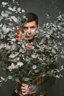 Крупный план татуированного молодого человека, держащего в руках сухое растение, на сером фоне