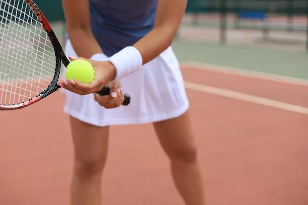 ラケットでボールを打つテニスプレーヤーのクローズアップ。