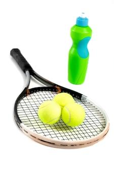 テニス ラケット、ボール、白地に水のボトルのクローズ アップ