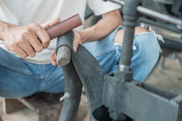 オートバイ修理店で漏れのあるインナーチューブをこすりながらタイヤ修理業者の手のクローズアップ