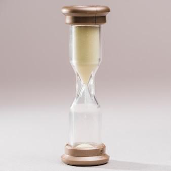 Крупный план прозрачных песочных часов на цветном фоне