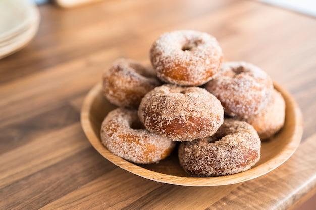 Закройте поднос свежеиспеченные домашние сахарные пончики на деревянный стол на кухне