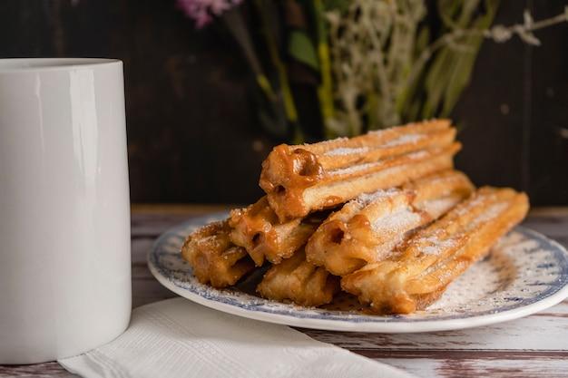 오래된 판에 있는 빈티지 접시에 덜세 데 레체로 가득 찬 전형적인 히스패닉 츄로스를 닫습니다. 가로 프레임, 복사 공간.