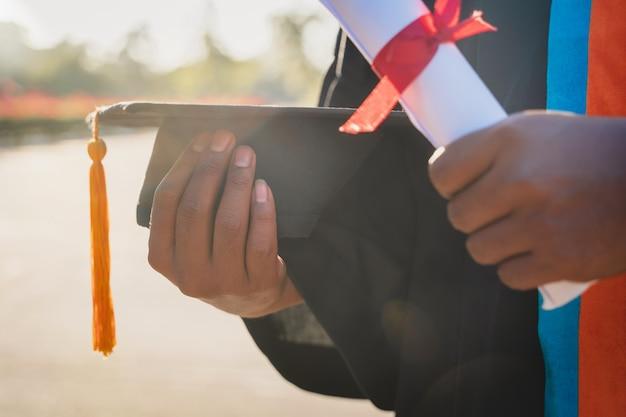 Крупный план выпускника университета с дипломом об окончании и минометной доской