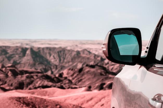 절벽 앞의 모래에 있는 차량의 클로즈업. 달의 계곡. 아프리카. 나미비아