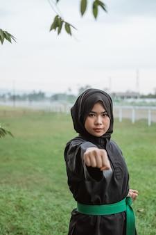 자연 속에서 한 손으로 치는 동작으로 pencak silat 유니폼을 입고 가려져있는 여자의 닫습니다