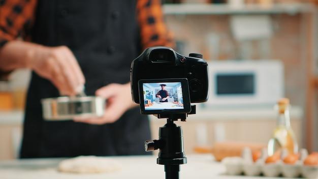 キッチン料理でシニア笑顔の男性ブロガーを撮影するビデオカメラのクローズアップ。ソーシャルメディア上でデジタル機器と通信するインターネット技術を使用する、引退したブロガーシェフのインフルエンサー