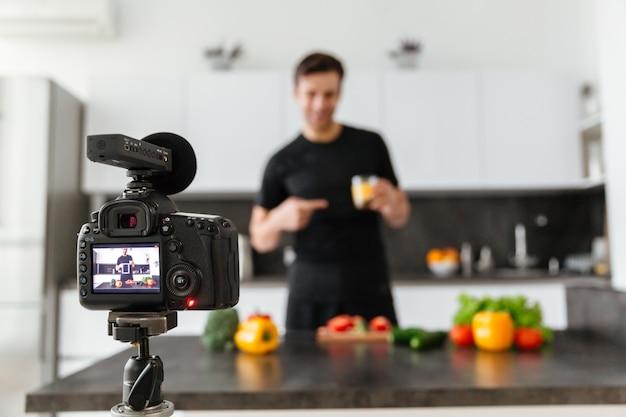 웃는 남성 블로거를 촬영하는 비디오 카메라의 클로즈업