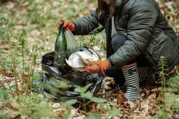 Крупный план добровольца, убирающего на природе стекло, пластик и прочий мусор.