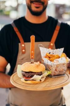 おいしいハンバーガー、フライドポテト、ソースを木の板で提供するウェイターのクローズアップ。