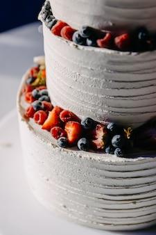イチゴとブルーベリーと白いクリームで覆われたウエディングケーキのクローズアップ
