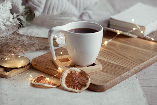 Крупным планом белая чашка с горячим напитком на размытом фоне с гирляндой.