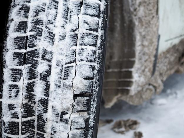 雪と氷で冬の車のタイヤのトレッドのクローズアップ。冬季に特別なタイヤを使用することは、安全なブレーキングと加速の基礎です。ハイテクゴムコンパウンド。