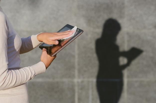 女性のクローズアップは、ナプキンで錠剤を消毒します。灰色のコンクリートの壁を背景に、はっきりとした影のあるシルエットが残ります。