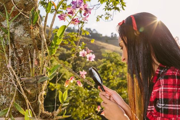 돋보기를 통해 꽃을 검사하는 여자의 근접 촬영