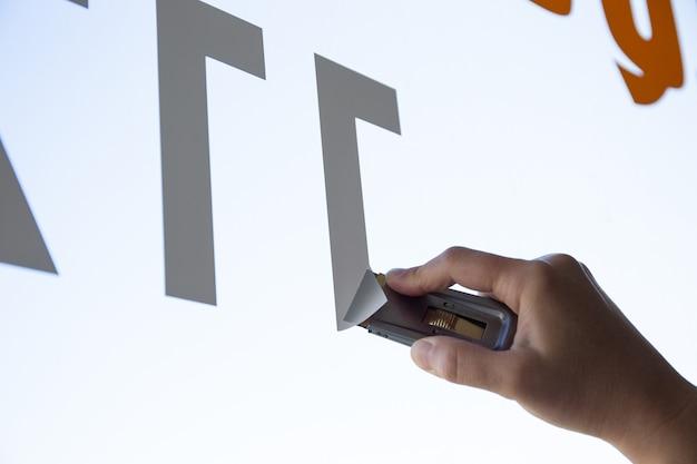 Крупным планом женская рука, удаляющая виниловую наклейку с окна с помощью скребка