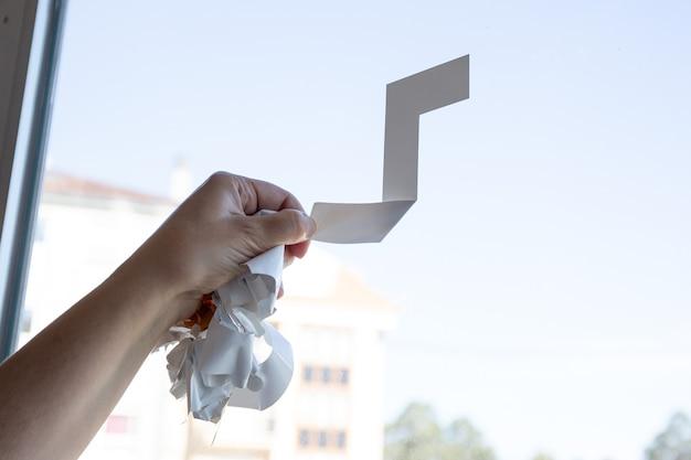 Крупным планом женская рука, удаляющая виниловую наклейку из окна с помощью инструмента. копировать пространство
