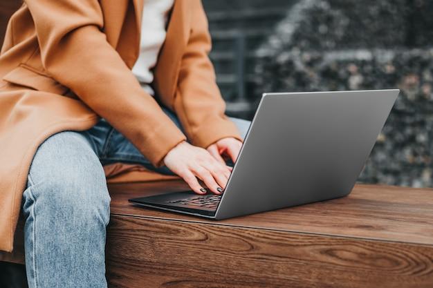 사무실 건물에 대 한 거리에서 노트북에 입력하는 여자 손의 닫습니다. 사업가 작동 거리. 확대