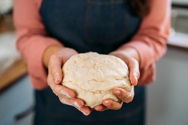 Крупным планом женщина, держащая тесто мяч, чтобы сделать пиццу в ее домашней кухне