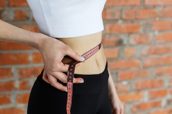 Close-up of a woman holding tape-measure on her fit waist
